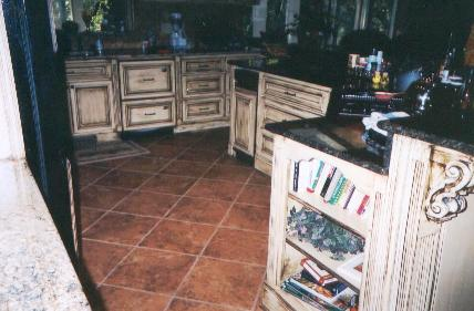 Dramatic tile floor, accent wall shelf, and angled island.